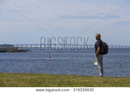 A Tourist On The Shores Of The Baltic Sea Looking At The Oresund Bridge, Malmo, Sweden