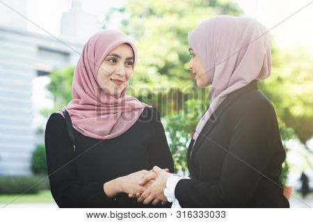 Muslim business women greeting, handshake and smiling.