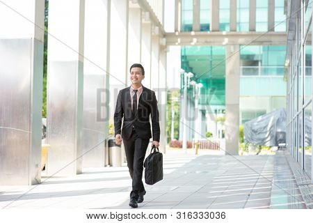 Businessman with suitcase walking outside office building.
