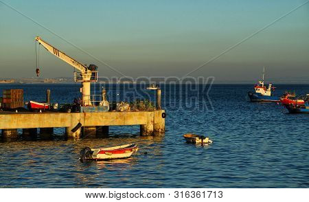 Cascais, Lisbon, Portugal- March 16, 2019: Boats And Crane In A Pier In Cascais Village At Sunset In