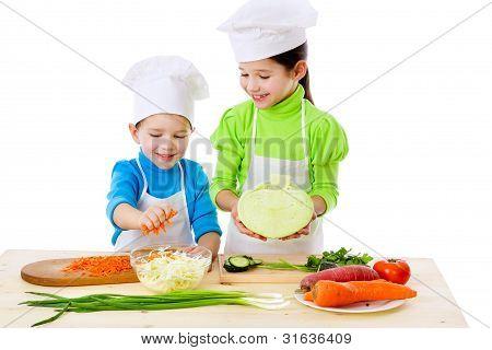 Two smiling kids preparing salad