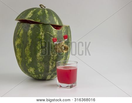The Watermelon C Tap To Fill The Juice On A Light Background. The Glass Of Fresh Juice  Watermelon.