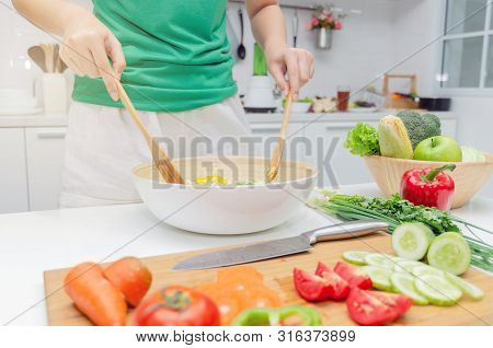 Diet. Young Pretty Woman In Green Shirt Standing And Preparing The Vegetables Salad In Bowl For Good