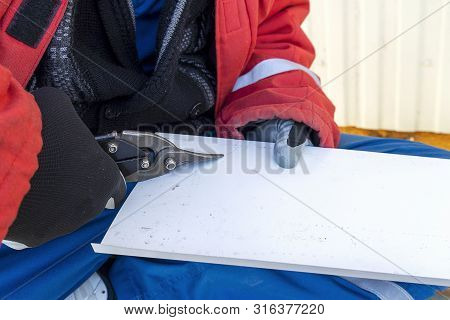 Builder Scissors Cuts A Steel Sheet. Worker Tin Cuts Out The Iron Roof. Hand With Scissors.