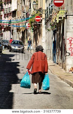 Lisbon, Portugal- March 17, 2019: Old Woman Carrying Bags In Bairro Alto Neighborhood. Narrow And Co