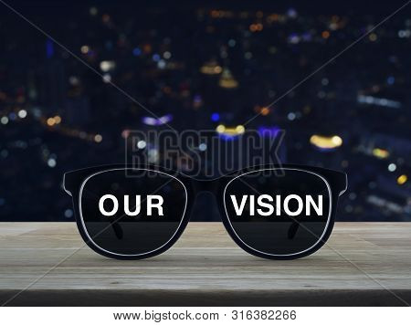 Black Glasses With Our Vision Text On Wooden Table Over Blur Colorful Night Light Office City Tower
