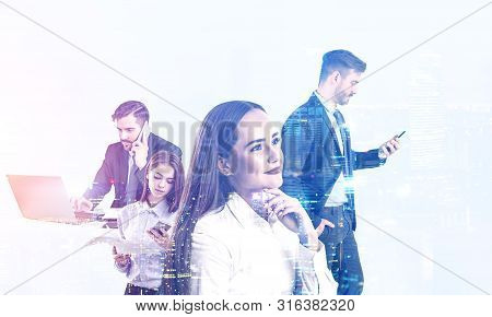 Portrait Of Diverse Business People Working With Gadgets With Double Exposure Of World Map Hologram.