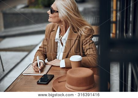 Smiling Mature Woman Writing In Notebook Stock Photo