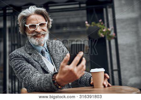 Happy Mature Gentleman With Smartphone Stock Photo