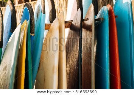 Set Of Colorful Surfboard For Rent On The Beach. Multicolored Surf Boards Different Sizes And Colors