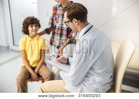 Doctor Treating Boy In Office Stock Photo