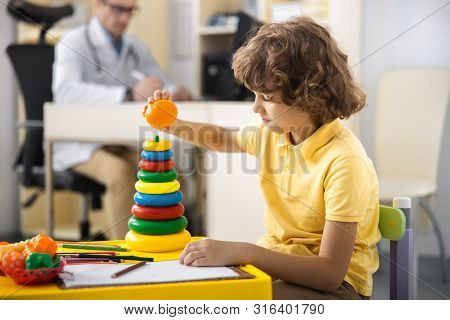 Curly Boy Playing With Pyramid In Clinic Stock Photo