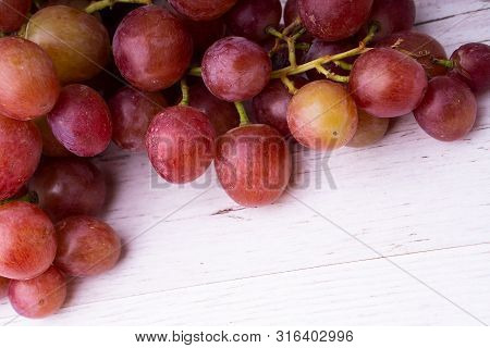 A Bunch Of Pink Grapes On A Wooden Light Tabletop.