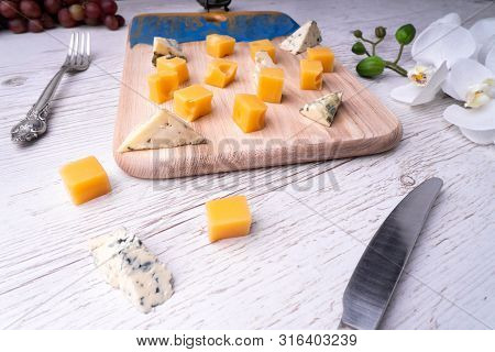 Cutting Board With An Abstract Pattern, Cheeses, Honey Grapes, Flowers, A Knife And A Fork.