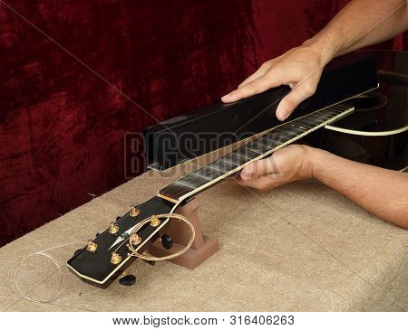 Musical Instrument Guitar Repair And Service - Worker Grinds Black Guitar Neck Frets.