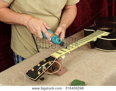 Musical Instrument Guitar Repair And Service - Worker Polishing Guitar Neck Frets Dremel And Paste G