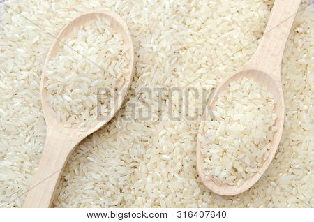 Polished White Rice In Wooden Spoon. Long Grain Rice And Round Grain Rice Background. Rice Pattern R