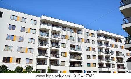 poster of Contemporary residential building exterior in the daylight. Modern apartment buildings on a sunny day with a blue sky. Facade of a modern apartment building