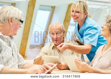 Nursing help has fun with seniors while learning in the computer course in the retirement home