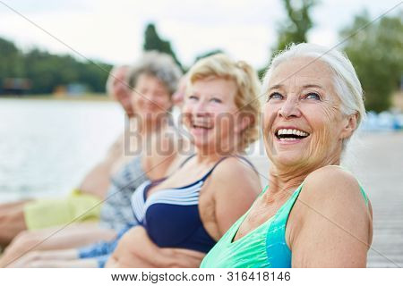 Laughing senior woman as a retiree in a bathing suit with friends on vacation at the lake