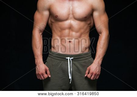 Strong Athletic Man - Fitness Model Showing His Perfect Body Isolated On Black Background With Copys