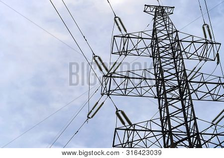 An Iron Electric Pole Holds Wires. High Voltage Communication Line. Transmission Of Electric Watts.