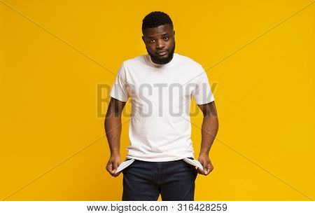 Poverty And Absence Of Money. Unemployed Sad African American Man Showing Empty Pockets, Yellow Stud