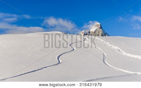 Freeride Tracks On Powder Snow With Mountain Peak Background