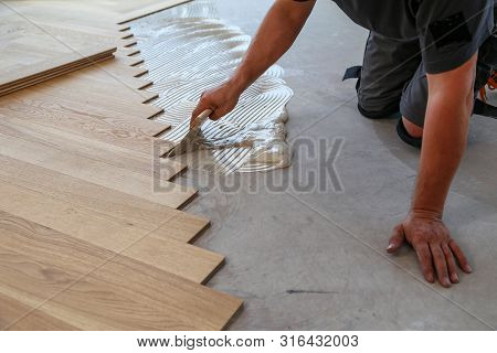 Worker Laying Parquet Flooring. Worker Installing Wooden Laminate Flooring