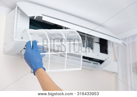 Technician Cleaning Air Conditioner. Hand Holding Air Conditioning Filter