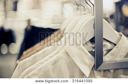 Shirts On Hangers. Shopping In Store. Clothes On Hangers In Shop For Sale. Blur Background. Fashiona
