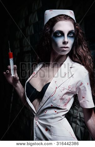 Horror Shot: The Strange Mad Nurse (doctor) In Bloody Uniform, With Syringe In Hand. Zombie Woman (l
