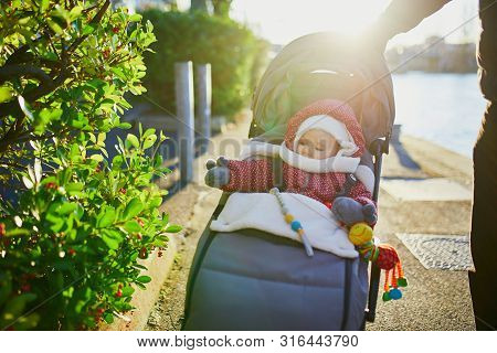 Adorable Little Girl In Red Jacket And White Knitted Hat And Scarf Sitting In Pushchair Outdoors On