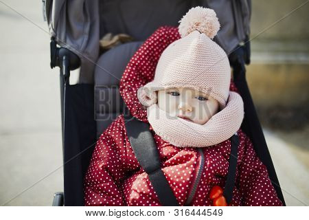 Adorable Little Girl In Red Jacket And Pink Knitted Hat Sitting In Pushchair Outdoors On A Fall Day.