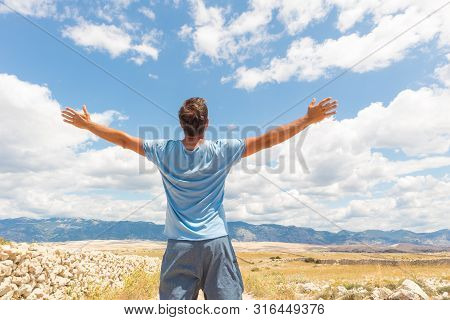 Rear View Of Casual Sporty Man Standing On A Dirt Country Road Rising Hands Up To The Clouds On A Bl