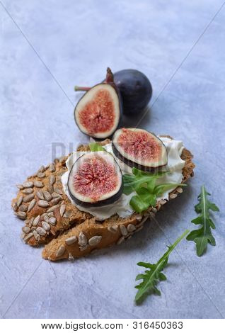 Closeup Of Healthy Open Sandwich With Cream Cheese And Figs On Dark Bread With Sunflower Seeds On Gr
