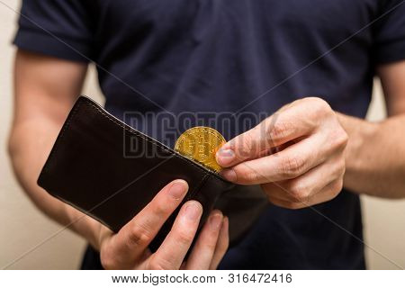 Man Takes Golden Bitcoin Out Of His Wallet, Virtual Currency. Crypto Currency. New Virtual Money. Bu