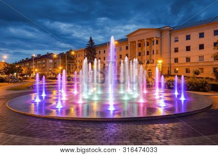 Fountain In Banska Bystrica At Night. Multicolor Water Fountain In Historical City Centre In Banska