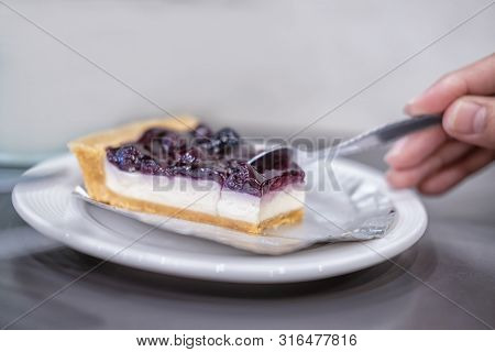 Woman Hand Holding Spoon To Eating Blueberry Cheesecake.