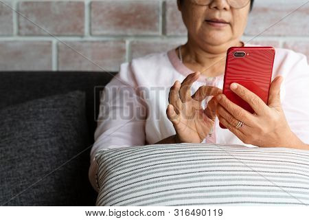Senior Woman Using Mobile Phone While Sitting On Sofa At Home