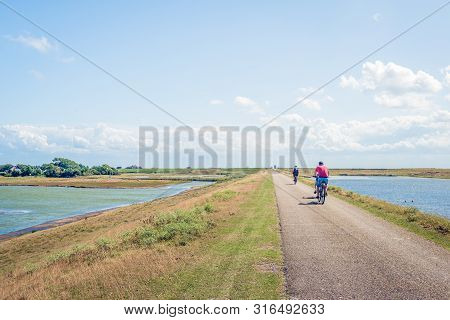 Unidentified Cyclists On A Dutch Dike On A Sunny Day In The Summer Season. The Photo Was Taken Near