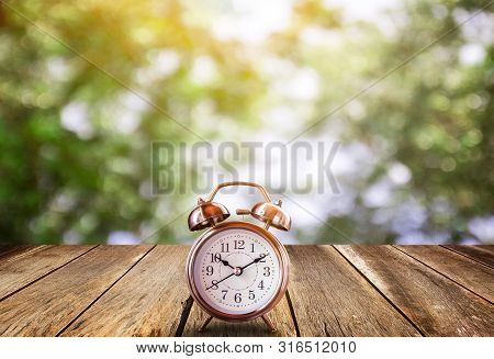 Retro Alarm Clock On A Wooden Table With Blured Bokeh Background. Save Time Savings Daylight Up Retr