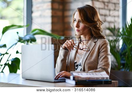 Confident Young Woman In Smart Casual Clothes, Working On A Laptop, Sitting By The Window In A Creat