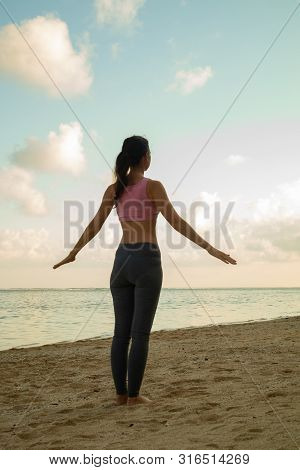 Fitness Woman Working Out At The Beach. Young Woman Doing Exercise. Sport At The Beach. View From Ba