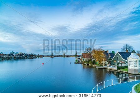 Twilight View Of Typical Dutch Houses With Windmills And The River Zaan At Zaanse Schans Netherlands