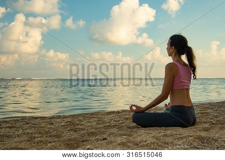 Lotus Yoga Pose. Yoga At The Beach. Young Woman Sitting On Sand, Meditating, Practicing Yoga And Pra