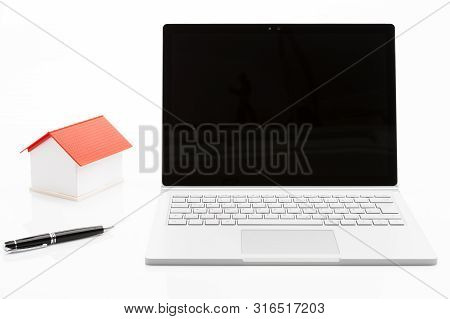 Image Shows A Laptop With A House And A Pen Isolated On White