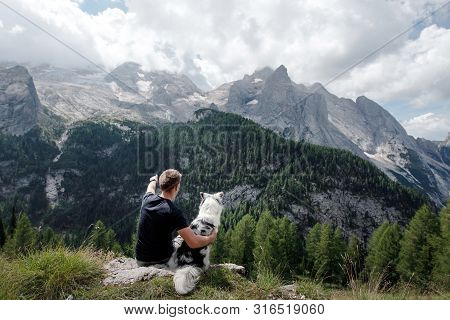 Australian Shepherd Dog With A Man In The Mountains At Sunrise. Travel With A Pet.