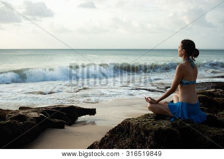 Young woman meditating, practicing yoga and pranayama with gyan mudra at the beach. Lotus yoga pose with gyan mudra. Sunset time. Caucasian woman sitting on the rock. Yoga retreat in Bali, Indonesia
