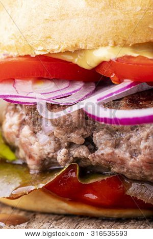 Closeup Of A Hamburger With Onions On Wood